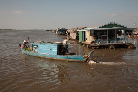 Boy steers the boat, which comes up from the streets of the village on the water Tonle Sap Lake in Cambodia.