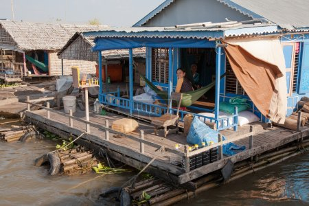 On the terrace of the house of the village on the water Tonle Sap Lake in Cambodia in a hammock relaxing family.