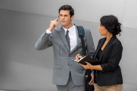 Photo pour Exécutif d'affaires et assistant voyageant à la convention lors d'un voyage à l'aéroport prendre des notes portrait réussi concept de travail d'équipe de couple - image libre de droit