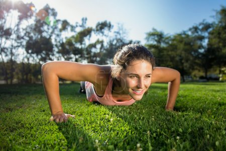 Powerful athlete woman strength training pushups outdoors in the morning