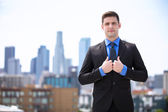Confident businessman in a suit standing tall and proud attorney buildings in background