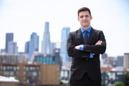 Young business man attorney arms folded proudly standing in the city building background