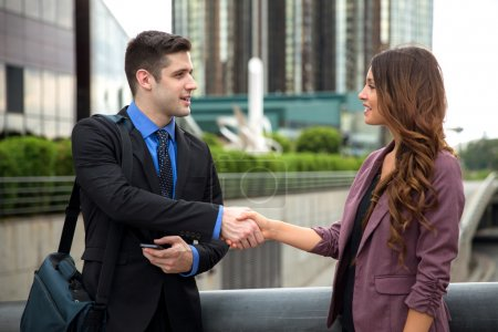 Two businesspeople shake hands traveling meeting greeting salesperson in sales career