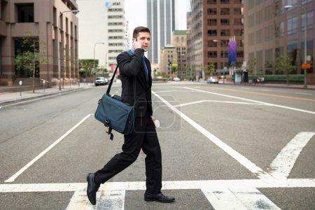 Photo pour Lifschitz homme traversant la rue sur la façon de travailler tard pour nomination sur les bâtiments du centre de la cellule pone - image libre de droit