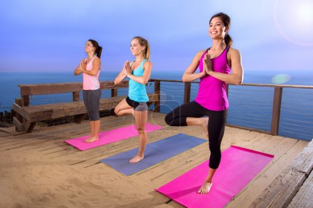 Yoga retreat nature outdoors women at beautiful location hill landscape ocean travel