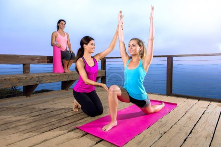 Yoga teacher instructor guru assists beginner student exercise stretch pose outdoors