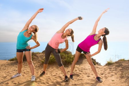 Stretching women outdoors on hike hill near ocean overlooking beach reach toward the sky