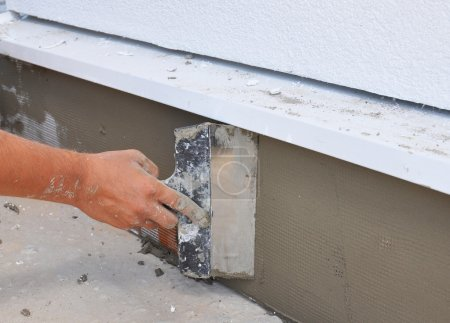 Man's hand plastering a wall insulation and house foundation with trowel