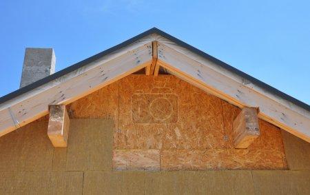 Attic new house facade insulation against blue sky