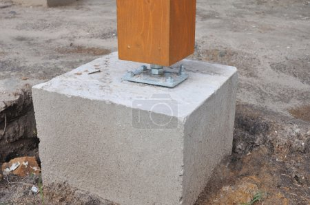 Closeup of wooden pillar on the construction site with screw for
