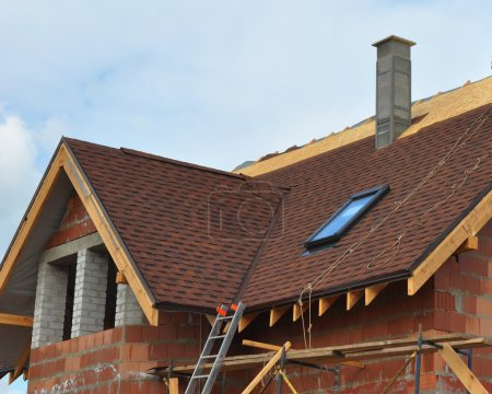 Roofing and building new house with modular chimney, bitumen tile, skylights and eaves.