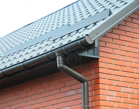 Closeup on new rain gutter system and roof protection from snow