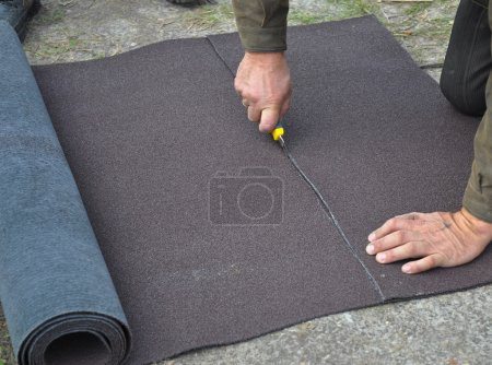 Roofer cutting roll roofing felt or bitumen during waterproofing