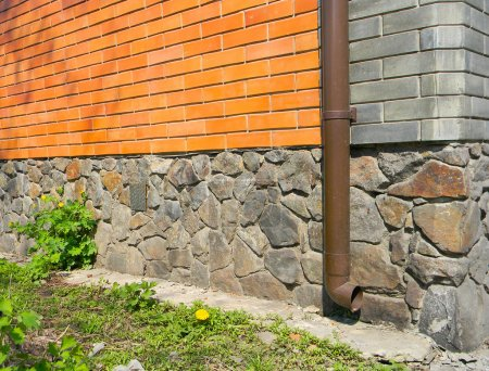 Rain gutter without any drainage systems near house foundation.