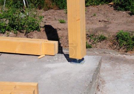 Photo pour Pilier en bois sur le chantier béton avec vis. Les piliers en bois sont des structures qui peuvent être placées sur des fondations ou des plateformes . - image libre de droit