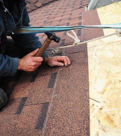 Photo pour Couvreur installe les bardeaux bitume avec marteau et des clous - gros plan sur les mains. Travaux de toiture. - image libre de droit