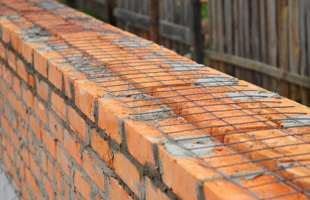 Close up on laying building bricks with iron grid ...