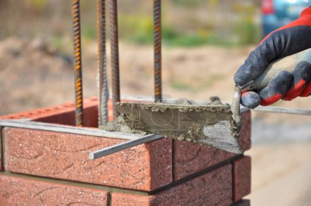 Bricklaying closeup. Bricklayer hand holding a putty knife and building a brick fence column.