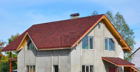 New House Roof Covered with Bitumin Tiles. Asphalt Shingles Roof