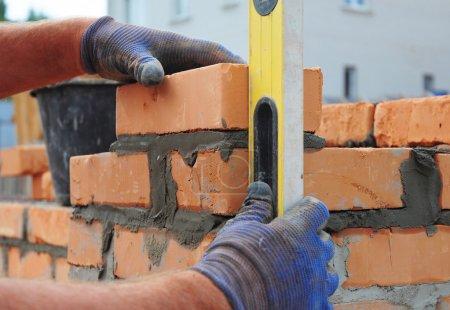 Photo pour Maçon à l'aide d'un niveau à bulle pour vérifier le nouveau mur de briques rouges en plein air. Briquetage bases Techniques de la maçonnerie. - image libre de droit