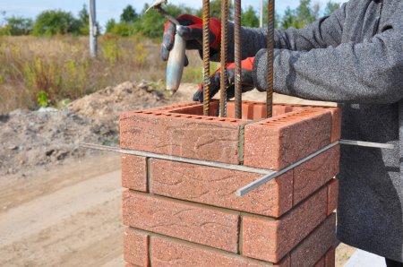 Bricklayer Worker Installing Red Clinker Blocks around Iron Bar
