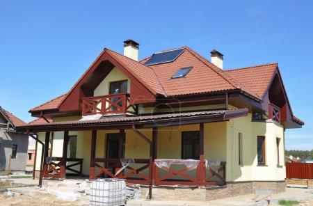 Photo pour Système solaire de chauffage de l'eau sous vide gouttière de pluie sur le toit de la maison carrelée rouge. Énergie orale pour l'efficacité énergétique Nouveau concept de construction de maison Extérieur - image libre de droit