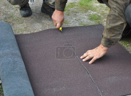 Roofer  cutting roll roofing felt or bitumen during waterproofin