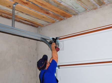Contractor Installing Garage Door Post Rail and Spring Installation and Garage Ceiling.