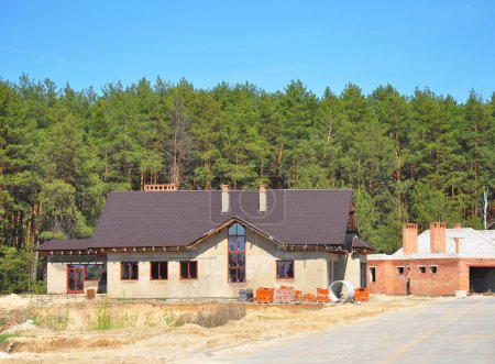 Building New Suburban House on the Forest Background. Plastering Wall, Metal Roofing, Chimney, Garage, Insulation and Construction Site