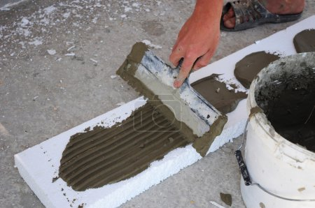 Man's Hand Plastering a Wall Styrofoam or Foam Board Insulation with Trowel.