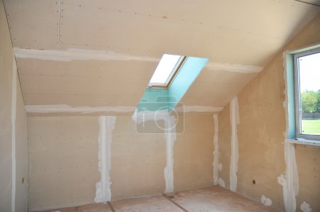 Attic room under construction with gypsum plaster boards