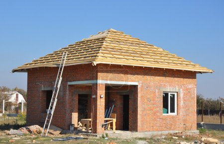 Roof Membrane Coverings Wooden Construction Home Framing with Roof Rafters and Metal Ladder Outdoor against a Blue Sky. Roofing Construction Exterior with Red Brick house Wall Facade.
