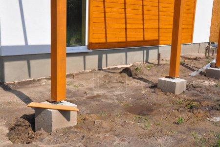 Wooden pillar on the construction site with screw and place for terrace.