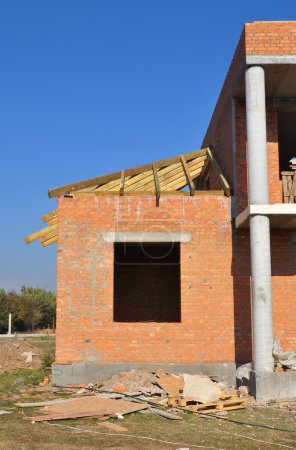 New brick building house construction with doorway columns, wind