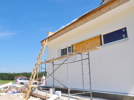 Facade building, install window and roofing. House Construction.