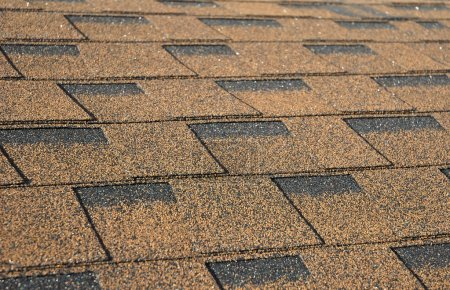 A newly installed composition asphalt shingle roof. Close up on brown roof shingles as a textured background