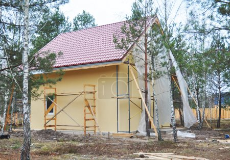 Construction or repair of the rural house with balcony, eaves, windows, chimney, roofing, fixing facade, insulation, plastering and using color. House construction.