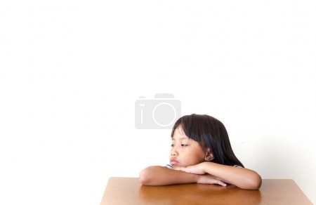Bored children girl sitting at the table