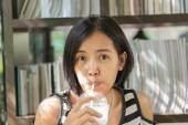 Asijská žena v bílé a černé košile pití kávy v kavárně