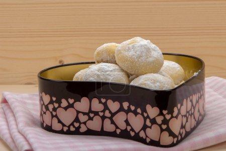 Photo pour Petits biscuits faits maison en sucre en poudre dans une boîte en fer blanc en forme de coeur sur une serviette à carreaux en coton - image libre de droit