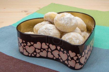 Photo pour Petits biscuits faits maison en sucre en poudre dans une boîte en étain en forme de coeur sur une serviette de coton rayée - image libre de droit