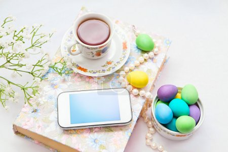 Phone with a cup of tea and pearl necklace with flowers on a white satin background. A book, tea cup, telephone and decoration. Tea time and easter painted eggs