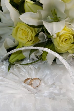 Wedding bouquet of lilies and roses, gold wedding rings on a cushion