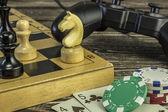 Gamepad, šachovnice s postavami a hrací karty s čipy na stole. Zaměřit se na koni šachy