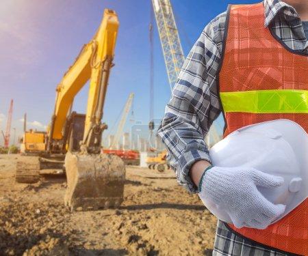 Photo pour Builder avec casque jaune et des gants de travail sur chantier - image libre de droit