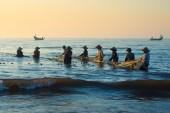 Fishermen on the beach in sunrise