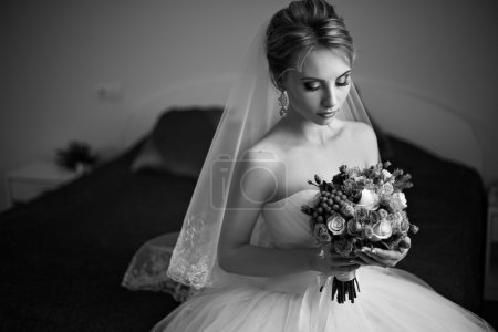 Beautiful bride with bouquet sitting on a bed. Black and white photo.