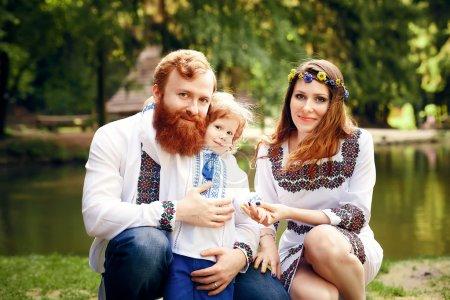 Photo pour Heureuse famille ukrainienne avec petit fils en robe ukrainienne traditionnelle dans une campagne, parc - image libre de droit