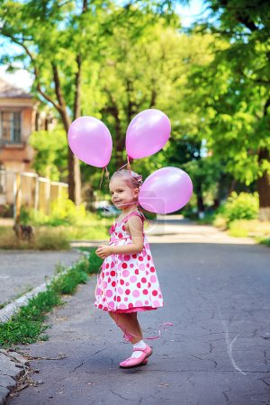 BNeautiful little girl plays with the pink air ballons, emotionally