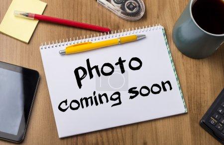 Photo pour Photo à venir bientôt - Note Pad avec du texte sur table en bois - avec des outils de bureau - image libre de droit